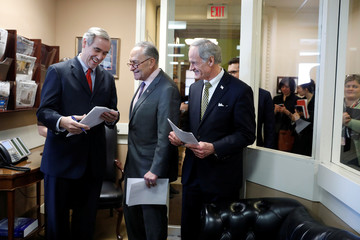 Senate Minority Leader Chuck Schumer speaks with Senator Jeff Merkley (D-OR) and Senator Tom Carper (D-DE) prior to holding a news conference at the U.S. Capitol in Washington