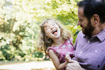 Caucasian father carrying laughing, daughter