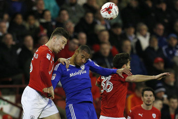 Barnsley's Angus MacDonald (L) and Mathew James (R) in action with Cardiff City's Kenneth Zohore
