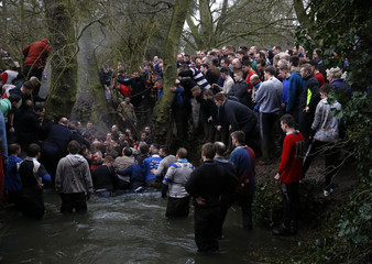Players stand in a river as they compete for the ball during the annual Shrovetide football match in Ashbourne