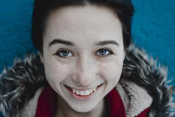 Smiling Caucasian woman near blue wall