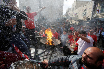 People celebrate the arrival of the 'Holy Fire' from Jerusalem's Holy Sepulchre outside the Church of the Nativity in the West Bank town of Bethlehem