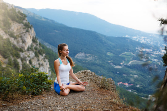 Young woman meditating outdoors, girl doing yoga high in the mountains, relaxation self-reflection concept