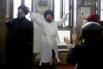 An Ultra-Orthodox Jewish man wearing a clown nose takes part in an annual parade marking the Jewish holiday of Purim, in Jerusalem