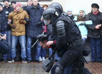 Law enforcement officers detain a man during a gathering which marks the anniversary of the proclamation of the Belarussian People's Republic in Minsk