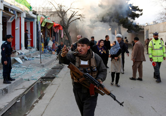An Afghan policeman reacts at the site of a blast in Kabul, Afghanistan