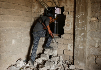Iraqi Federal Police moves through a hole at Bab al Jadid district as the battle against Islamic State's fighters continues in the old city of Mosul