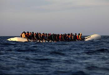 A plastic raft overcrowded by migrants is seen drifting during a search and rescue operation by Spanish NGO Proactiva Open Arms in central Mediterranean Sea, some 22 nautical miles north of the Libyan town of Sabratha