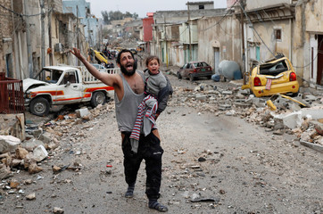 A man cries while carrying his daughter as he walks from Islamic State controlled part of Mosul towards Iraqi special forces soldiers during a battle in Mosul