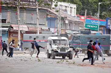 Kashmiri protestors hurl pieces of bricks and stones towards Indian police vehicles during a protest in Srinagar