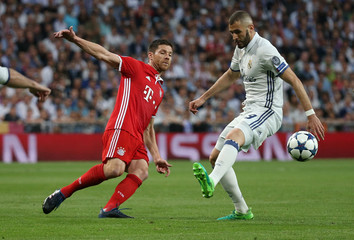 Bayern Munich's Xabi Alonso in action with Real Madrid's Karim Benzema