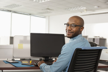 Smiling African American man using computer in office