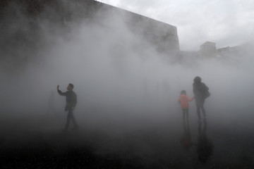 People interact with the installation 'London Fog (2017)' by Japanese artist Fujiko Nakaya at the Tate Modern in London