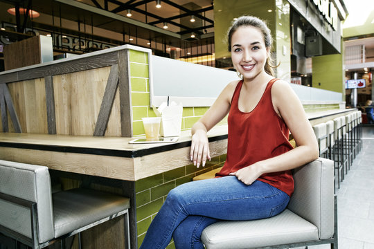 Smiling Mixed Race woman posing in food court