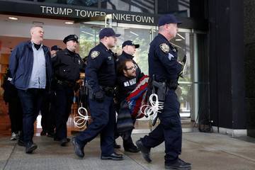 New York City Police officers (NYPD) carry and escort protestors after making arrests for demonstrating in Trump Tower in New York City
