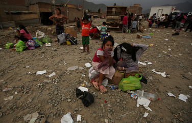 Residents sit on their belongings on a street after rivers breached their banks due to torrential rains, causing flooding and widespread destruction, in Huachipa, Lima