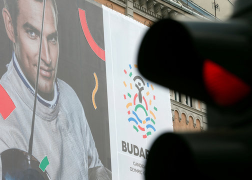 Traffic lights switch to red in front of a Hungarian pro-Olympics billboard with two-times sabre fencing Olympic champion Szilagyi advertising the Games in central Budapest