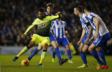 Brighton's Dale Stephens in action against Reading's Lewis Grabban (L)