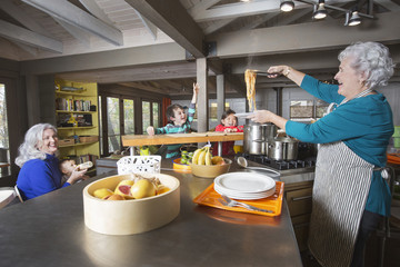Grandmothers and grandchildren having fun in kitchen