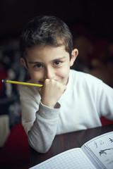 Smiling Hispanic boy practicing writing alphabet