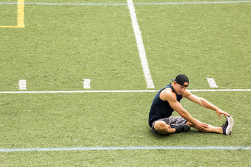 Young man stretching leg while sitting on sports field