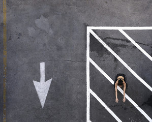 Aerial view of Pacific Islander woman doing squats in parking lot