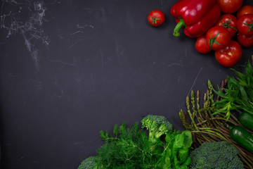 Fresh spring colorful vegetables on black chalkboard