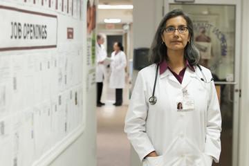 Serious Mixed Race doctor standing in hospital corridor