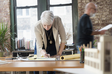 Older Caucasian businesswoman writing in office