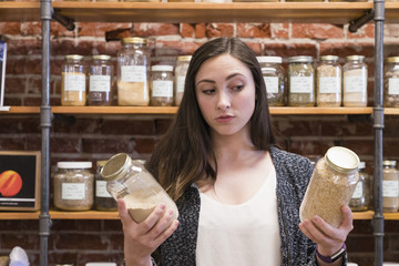 Woman comparing jars in nutrition store