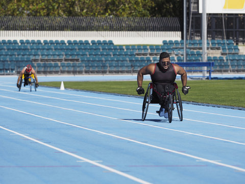 Middle Eastern man racing in wheelchair on track