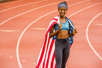 Smiling Black athlete posing with American flag on track