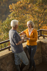 Older Caucasian couple enjoying wine and scenic view