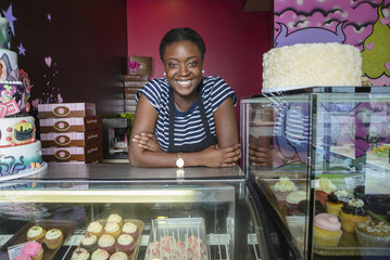 Black business owner leaning on bakery display case