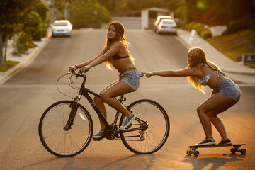 Girl riding bicycle pulling friend on skateboard