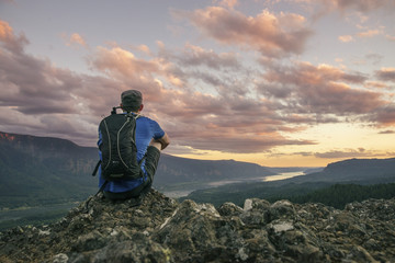 Rear view of hiker with backpack sitting on mountain at Crater Lake National Park
