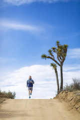 Male hiker running on road at Joshua Tree National Park against sky during sunny day