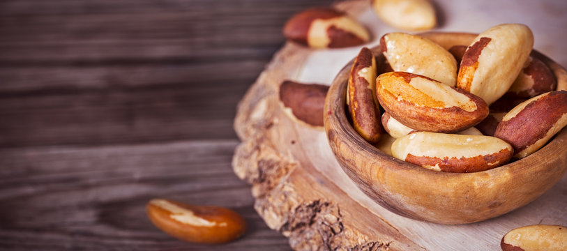Bowl of peeled brazil nuts on wooden background with copy space