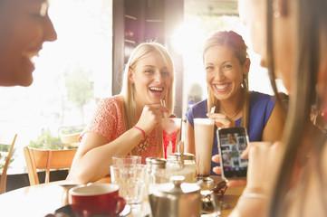 Women drinking milkshakes with straws at restaurant