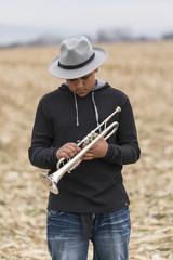 Mixed Race teenage boy holding trumpet in field