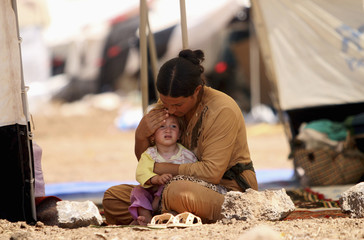 A refugee woman from the minority Yazidi sect, who fled the violence in the Iraqi town of Sinjar, sits with a child inside a tent at Nowruz refugee camp in Qamishli