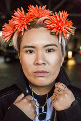 Portrait of serious androgynous Asian woman with flowers in hair