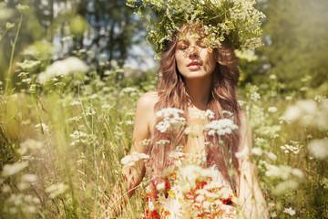 Caucasian woman enjoying wildflowers in field