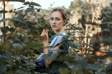 Young woman standing among bushes