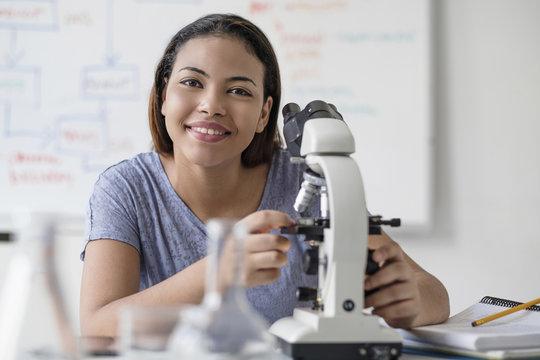 Smiling Hispanic woman using microscope