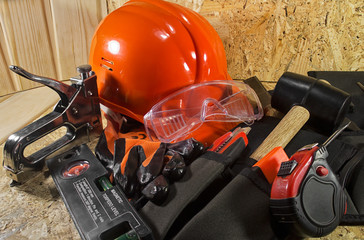 Red construction helmet, orange gloves, tools belt, rullers, stapler & worker glasses laying on a wooden board.