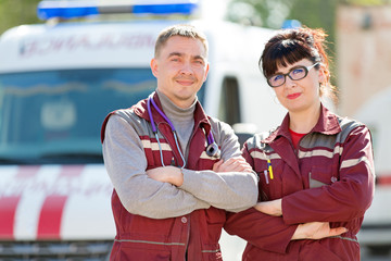 Doctor with colleague paramedic on ambulance vehicle background
