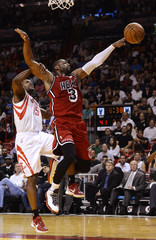 Miami Heat's Wade is fouled by Houston Rockets' Douglas during their NBA basketball game in Miami