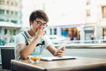 Young man using mobile phone in the city of Madrid. Young boy in the heart of madrid. Madrid centro. Hipster and student lifestyle. Wearing vintage clothes. Student boy sitting in a bar with mobile p