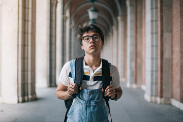 College student with his backpack serious and tired. Wearing vintage uniform